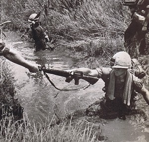 Vietnam War - First Infantry Division. Soldiers wade through swamp. Courtesy of First Infantry Division