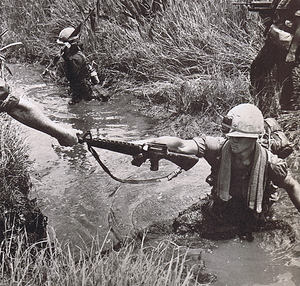 First Infantry Division soldiers wade through a swamp during the Vietnam War. Courtesy of First Infantry Division