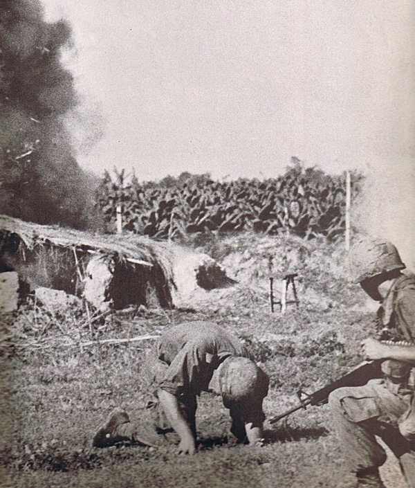 First Infantry Division soldiers take cover from an explosion during the Vietnam War.  Photo Courtesy of First Infantry Division.