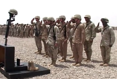 Soldiers of the 42nd Infantry Division, New York National Guard, pay respects to a fallen comrade at a memorial service in Iraq.