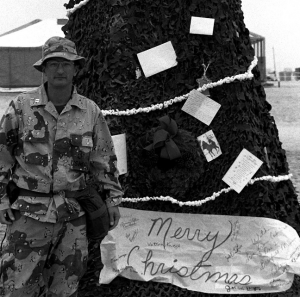 1st Marine Division Marine poses by Christmas tree.