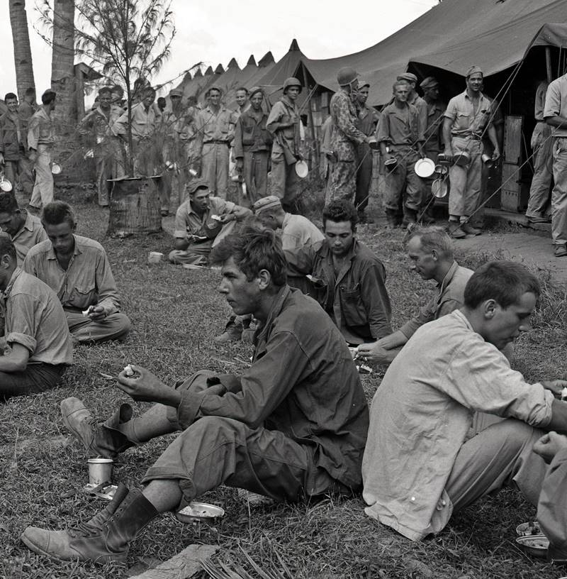 U.S. soldiers eat Christmas meals while other soldiers wait in line. The Philippines World War II