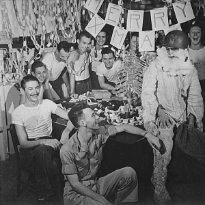WW2 Personnel of USS LEXINGTON celebrate Christmas with make-shift decorations and a firefighting, helmeted Santa Claus